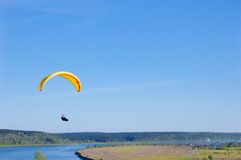 Yellow bright Paraglider in blue sky above the river and riverside. Bird`s eye panorama. Tom river. Tomsk city, Russia. Yellow Paraglider in blue sky above the Royalty Free Stock Photography