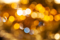 Yellow brown blurred shimmering Christmas lights. Abstract blurred background - yellow and brown shimmering Christmas lights of electric garlands on Xmas tree Royalty Free Stock Photo