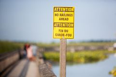 Yellow and Brown Boardwalk Sign Warning No Railing Ahead. A Yellow and Brown Boardwalk Sign Warning No Railing Ahead with Deed People in the background stock photography