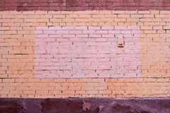 Yellow and brown brick wall with painted splotch Stock Image