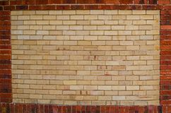 Yellow brown brick wall with red brick wall in border, space for text. A Yellow brown brick wall with red brick wall in border, space for text stock image