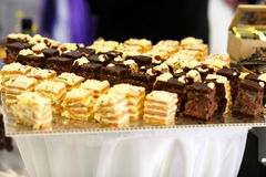 Yellow and brown cakes lie on a big tray Royalty Free Stock Photos