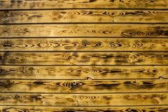 Yellow brown fence wall of natural wooden boards. horizontal lines. rough surface texture. A yellow brown fence wall of natural wooden boards. horizontal lines stock images