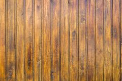 Yellow brown fence wall of wooden planks. vertical lines. rough surface texture. A yellow brown fence wall of wooden planks. vertical lines. rough surface royalty free stock images