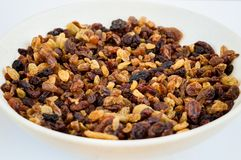 Yellow and brown raisins in a small white ceramic plate on the white table. Yellow and brown raisins in a small white ceramic plate Royalty Free Stock Photos
