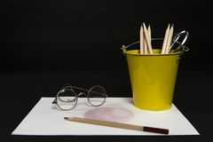 Yellow Bucket of Colored Pencils with a drawing and antique eye glasses. Horizontal Color Image of a Yellow Bucket of Colored Pencils with a drawing and antique Royalty Free Stock Photography