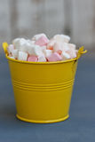 Yellow bucket full of marshmallow passage on Board against white boards Stock Images
