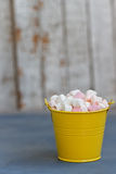 Yellow bucket full of marshmallow passage on Board against white boards Stock Image