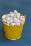 Yellow bucket with a marshmallow on blue wooden background Stock Images
