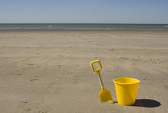 Yellow bucket and spade Royalty Free Stock Images