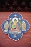 Yellow Buddha portrait painting on red wall , Nepal.  Royalty Free Stock Image