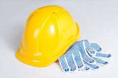 Yellow builder's helmet and work gloves over white Stock Photos