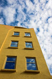 Yellow Building. A mustard yellow building against a blue sky with fluffy white clouds stock image