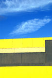 Yellow building against blue sky and clouds. Blue sky with feathery clouds behind a yellow and grey building.  Abstract colors and shapes.  Convention Center Stock Images