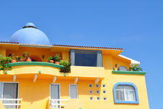 Yellow building with blue dome. Looking up at a yellow and blue building, against a bright blue sky.  Huatulco, Mexico Royalty Free Stock Photos
