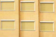 Yellow Building Facade with Six Closed Windows Shutters Royalty Free Stock Photos