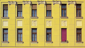 Yellow building face with windows. Yellow building face background with many windows Stock Image