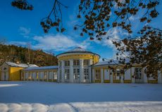 Yellow building of Ferdinand colonnade with mineral water at spa town Marienbad. Czech Republic, snow winter scene in park, shadows on ground, sunny day, blue stock photo