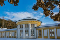 Yellow building of Ferdinand colonnade with mineral water at spa town Marienbad. Czech Republic, snowy winter scene in park, sunny day, blue sky, white clouds stock photo