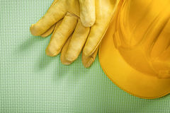 Yellow building helmet protective gloves on green background con Stock Image