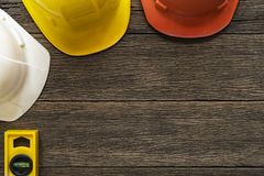 Yellow building level and helmets. On the old wood table Royalty Free Stock Image