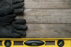 Yellow building level and old glove. On the old wood table, engineering work tool concept Royalty Free Stock Photography