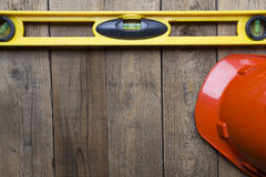 Yellow building level and red helmet. On the old wood table Stock Photography
