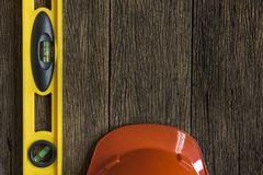 Yellow building level and red helmet. On the wood table Royalty Free Stock Photography