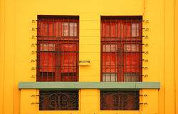 Yellow Building Wall. A bright yellow building wall with bars covering windows Stock Photography