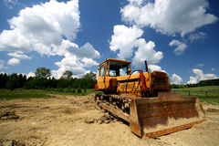 Yellow bulldozer. On the blue sky with white clouds Stock Photos