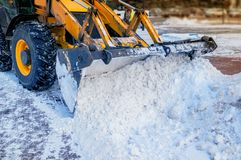 Yellow bulldozer clears the street after a heavy natural snowfall. Preparing for Christmas. Sunny frosty day. Close-up. The horizontal frame Royalty Free Stock Photo