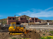 Yellow bulldozer on construction of villas Royalty Free Stock Photography
