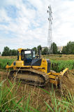 Yellow bulldozer creating route on riverbed Royalty Free Stock Image