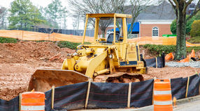 Yellow Bulldozer on Dirt Site. Large, heavy construction equipment on a fresh, dirt site behind silt fence stock photo
