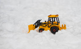 Yellow bulldozer, excavator toy snowplow placed in snow field, a royalty free stock photos