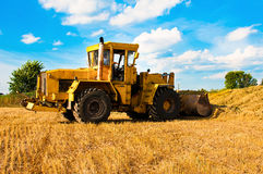 Yellow bulldozer in a field at harvest. On a Sunny day Stock Image