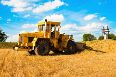 Yellow bulldozer in a field at harvest. On a Sunny day Stock Photo