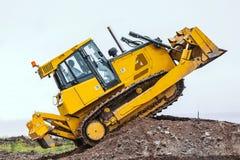 Yellow bulldozer overcome barrier. Dirty Yellow bulldozer overcome ground barrier, going up Royalty Free Stock Image
