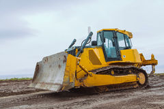 Yellow bulldozer overcome barrier Royalty Free Stock Photos