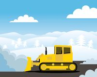 Yellow bulldozer pushing pile of snow. Hills covered with snow in background Stock Photography