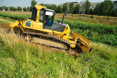 Yellow bulldozer on the riverbed Stock Photos