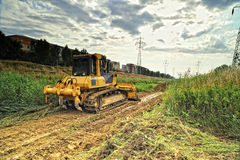Yellow bulldozer on the riverbed Stock Photography