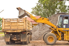 Yellow bulldozer was scooping soil into the truck. Royalty Free Stock Images
