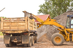 Yellow bulldozer was scooping soil into the truck. Stock Photos