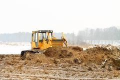 A yellow bulldozer working in the winter Royalty Free Stock Image
