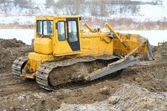 A yellow bulldozer working in the winter Stock Photo