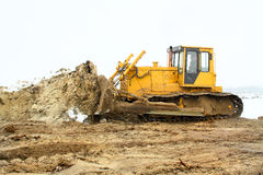 A yellow bulldozer working in the winter Royalty Free Stock Photo