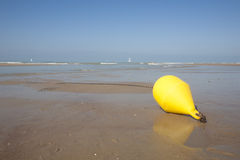 Yellow buoy at the beach Stock Image