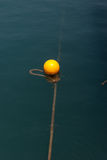 Yellow buoy on calm blue sea water surface Royalty Free Stock Photo