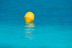 Yellow buoy floating in Mediterranean turquoise sea Royalty Free Stock Photo